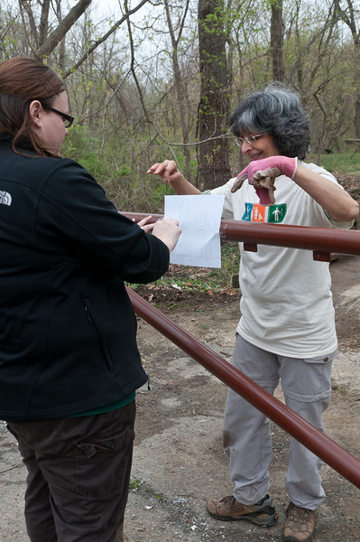 "Amanda Potter (foreground) and Maria Lameiro attach a ""Wet Paint"" sign to a freshly painted fence."