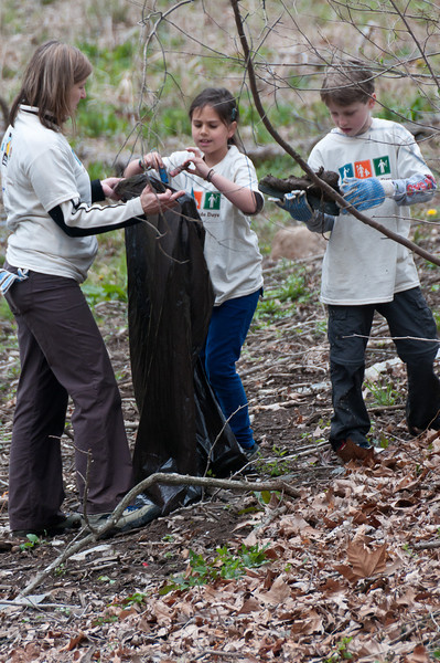 Pam Ficca holds a garbage bag for her children Ava Logan (8 years old) and Ramy Logan (10 years old) to fill with trash they picked up from the ground between the C&O canal and the Potomac River.
