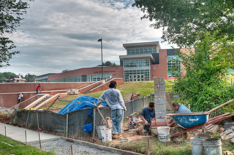 Workmen put the finishing touches on the grounds outside of Cabin John Middle School.