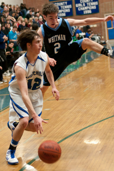 Jordan Bass of Churchill drives to the basket as Whitman's James Dionne leaps to block the way.