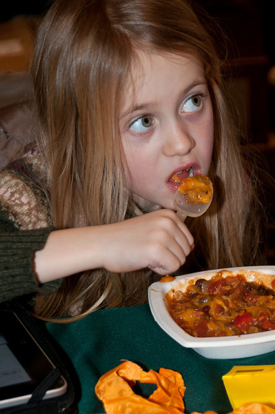 Six year old Jocelyn Norman takes a break from her iPad to eat her lunch of vegetable chili with macaroni and cheese.
