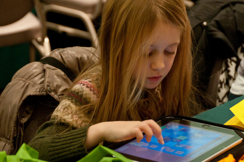 Six year old Jocelyn Norman came with her mother, Eris Normal (owner of Norman Farm Market).  Jocelyn amuses herself by playing games on her iPad.
