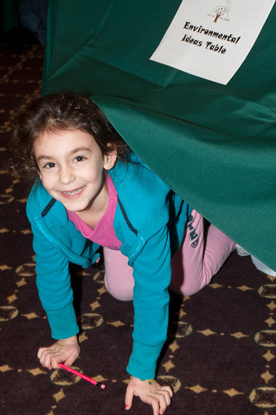 While the adults talk about the environment and green practices, 5 year old Miriam Yourman has fun playing hide-and-seek under the tables.