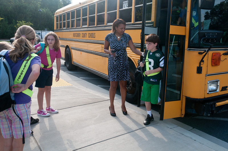 Assistant Principal Trish Thomas greets pupils arriving on the school bus.