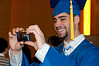 Brandon Varone takes a picture of his friends in their caps and gowns.