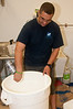 The dough will rise in a large bucket. The bucket is being coated with oil so the rising dough doesn't stick to it.
