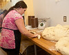 Brenda Bennaim rolls a piece of dough into a long cylinder where it will be coiled into a round loaf.