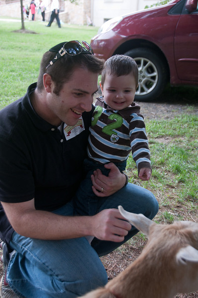 Zachary Mannes from Olney and his one-year-old son, Jonah are amused by the goat.