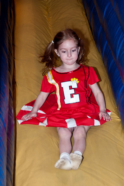 Cheerleader Abbie Glick (5 years old) goes down the slide.