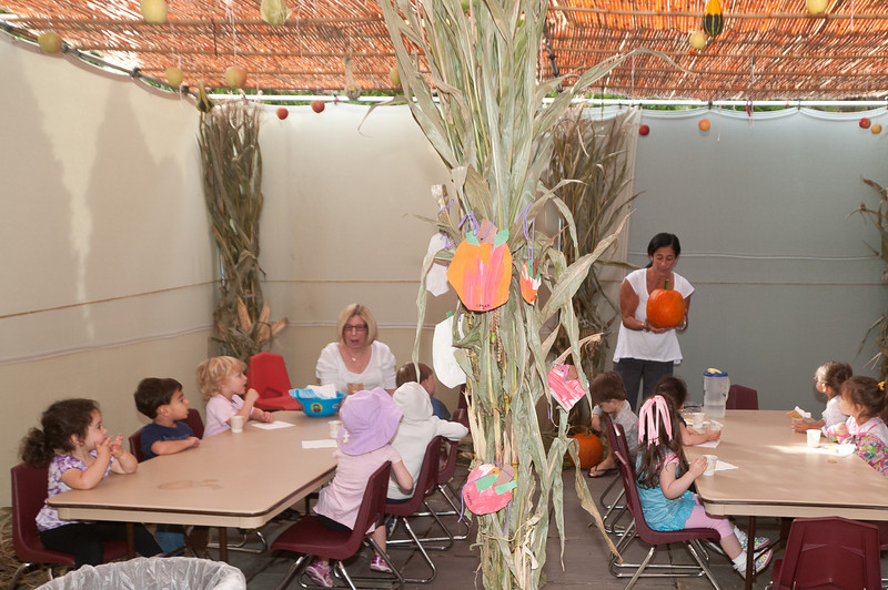 The two year old kids come into the decorated sukkah for a snack while learning about the items in the sukkah.