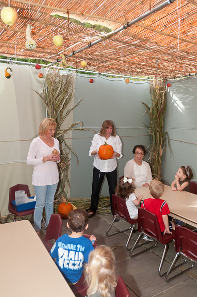 Fran Miller (flanked by Donna Toll and Phyllis Shankman) holds up a pumpkin to demonstrate the abundance of fall fruits and vegetables in the sukkah.