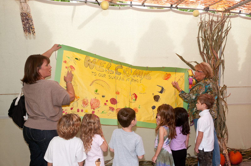 "Teachers Sandy Nesbit and Rita Weiss hand the ""Welcome to our Sukkah"" sign as several 4 year old students look on."
