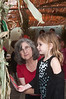 "Teacher Leslie Seiden watches as 4 year old Kate Schwartzburg hangs an ""apple"" in the sukkah."
