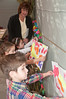 Teacher Joyce Sands helps her 4 year old students hand pictures in the sukkah.  (front to rear: Jake Gordon, Sammy Needle, and Ashley Antezana)