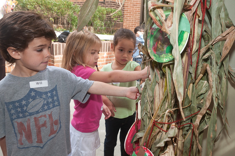 Will Spicer, Layla Taheri, and Kate Uhlfelder (all 4 years old) decorate a dried corn stalk in the sukkah.