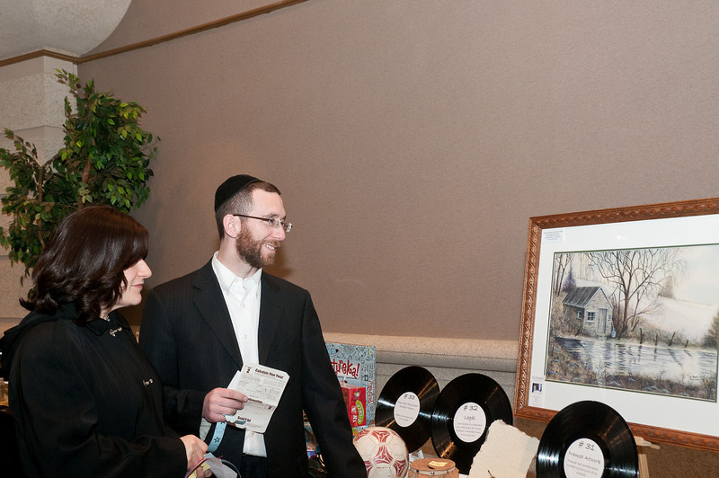 Chani and Shmuel Feldman consider putting in a ticket for the framed painting.