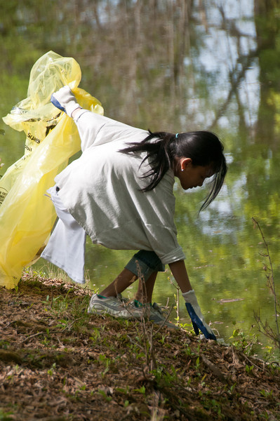 Vionny Amelia, 12 years old at Roberto Clemete MS, picks up trash along the bank of the C&O canal.