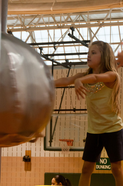 Christina Blessing (8 years old) pushes the heavy medicine ball at her fellow players.