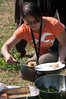 Volunteer Ling Tan samples the corn bread and fresh greens salad during the tour of the organic farm.