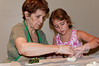 Madelyn Nader, Food Chair for the September bazaar, teaches 9 year old Emily Greenberg (Mill Creek ES) how to assemble spinach pies.