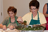 Madelyn Nader, Food Chair for the September bazaar, and Barbara Abraham assemble the spinach pies.