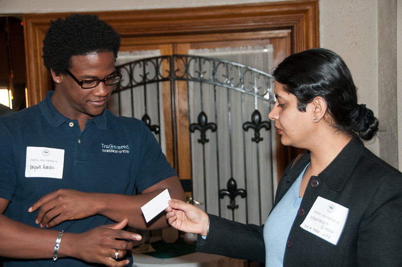 Dr. Bryant Harris of TruCentered takes a business card from Manpreet Singh of New York Life Insurance Company.