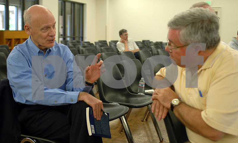 Dr. Hugh Ross speaks with an attendee at a conference on creation in Birmingham, Alabama.
