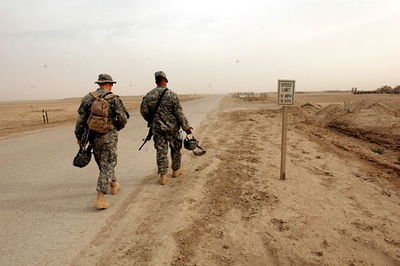 Two soldiers from the 1016th walk down the road to a meeting in Camp Cedar.