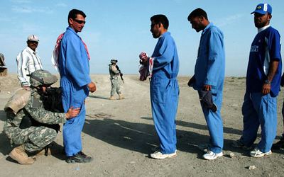 May 25, 2006:<br /> Spc. James Beyeler searches an Iraqi workers prior to transporting them to Camp Cedar for work. They pick up the workers on a road outside of Al Nasiriyah.