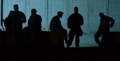 May 18, 2006:<br /> Soldiers take a cigarette break while waiting for mechanics to fix a broken fan belt on one of the HETs prior to leaving Camp Striker.