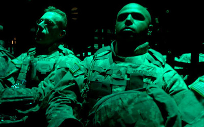May 11, 2006:<br /> Sgt. First Class Sean Keller, left, and Staff Sgt. Ryan Wiggins are bathed in green light during the flight to Iraq in a C-130 transport plane.