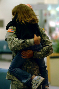 May 1, 2006: Master Sgt. Samuel Tlumac, of Manchester, Maine, hugs his daughter goodbye at the Bangor, Maine airport. It was the final stop on American soil for the 1016th.