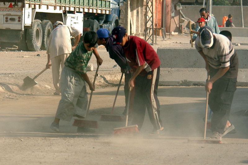 Cleaning up the Hay al Adel neighborhood begins with the youth sweeping the streets.