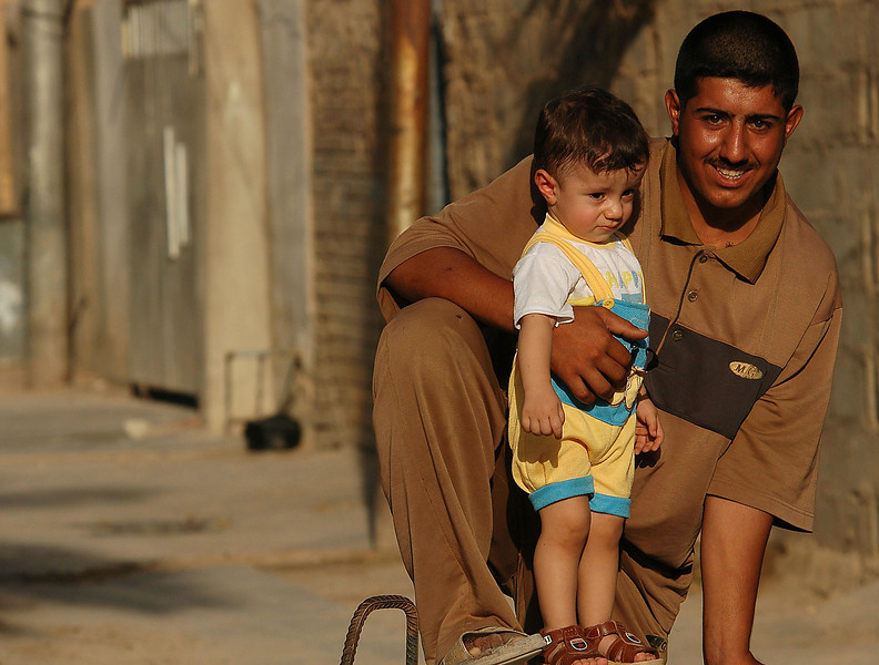 A father with his son watches the eveing patrol walk through his neighborhood.