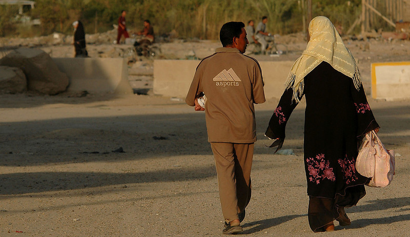 An Iraqi couple walk home in the early evening light after completing their shopping in Hay al Adel.