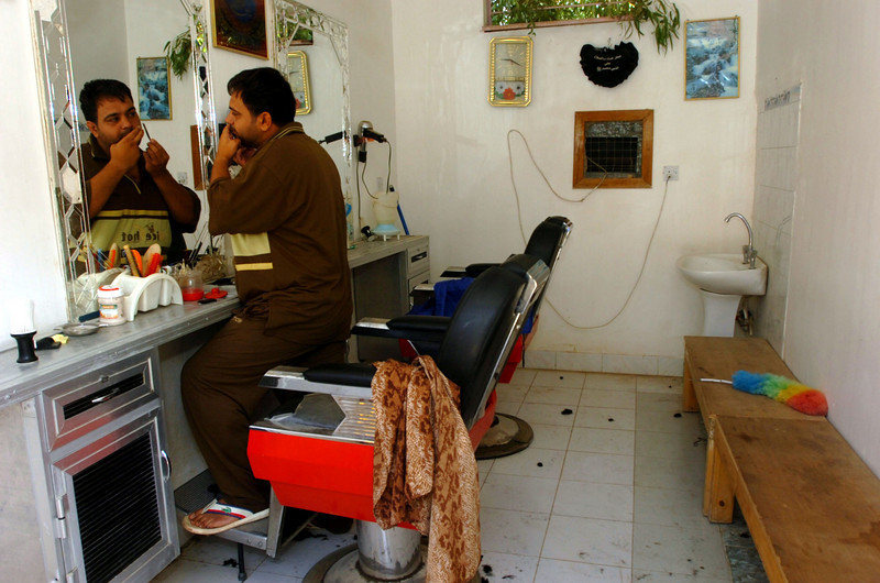 A barber gives himself a trim after opening his shop Saturday morning.