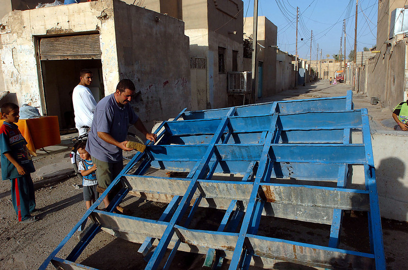 Reconstruction continues in the Hay al Adel neighborhood of Ramadi, as this man preps and paints shelves to re-open his shop.