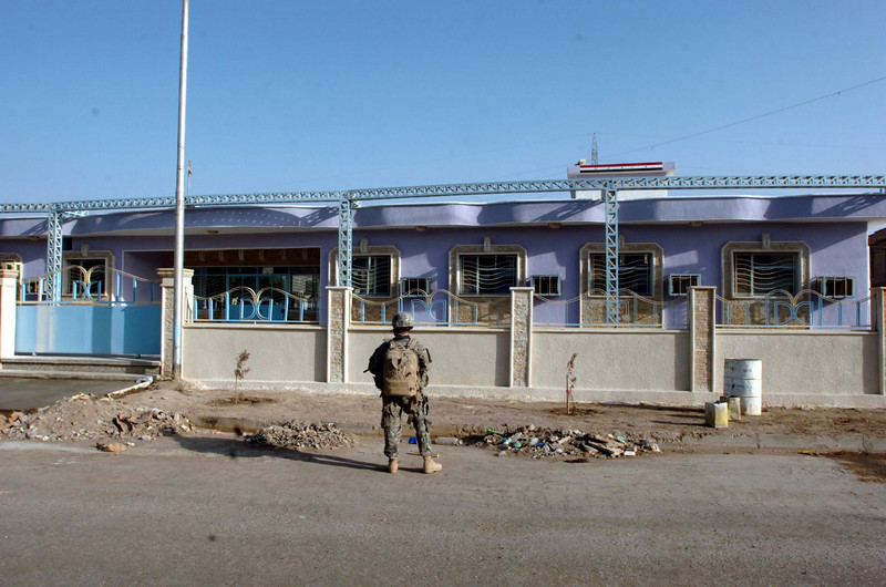 A soldier pauses in front of the recently renovated medical center in Hay al Adel.