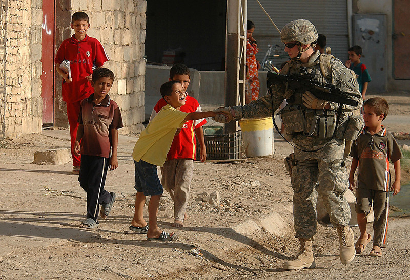 On evening patrol in Hay al Adel, a soldier shakes the hand of a young boy.