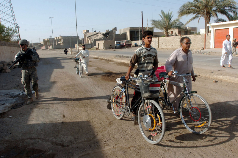 Iraqi nationals walk their bicycles past the patrol.