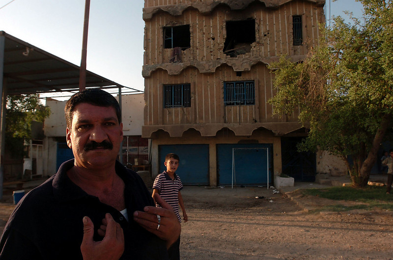 """Two years, two years,"" this disgruntled Iraqi man said, gesturing towards his scarred and bullet-riddled home, as the patrol walked past."
