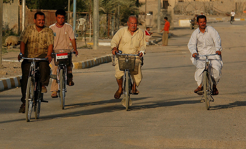 "Four men riding their bikes in the early evening approach the patrol, the elderly man, second from right, shouted an exuberant, ""Thank you,"" to the soldiers as they rode by."