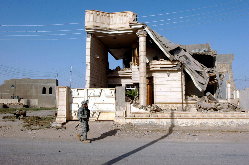 A soldier walks past a house destroyed during the insurgency in Ramadi.