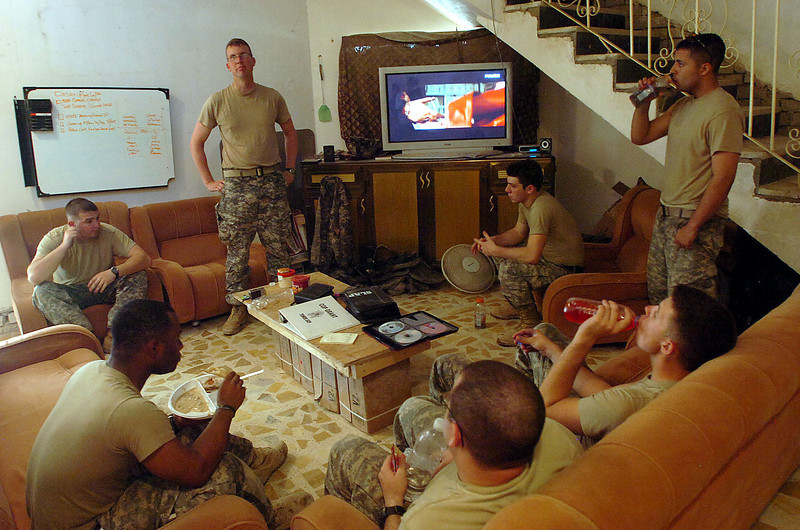 1st Lt Chad Raburn leads a briefing following the morning patrol of Hay al Adel in the living room of Combat Outpost Grant.