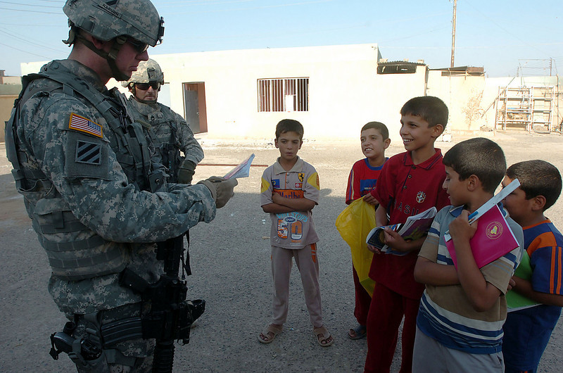 1st Lt Chad Raburn looks at a school boy's work book in the schoolyard. The boys were eager to practice their English language skills with the soldiers.