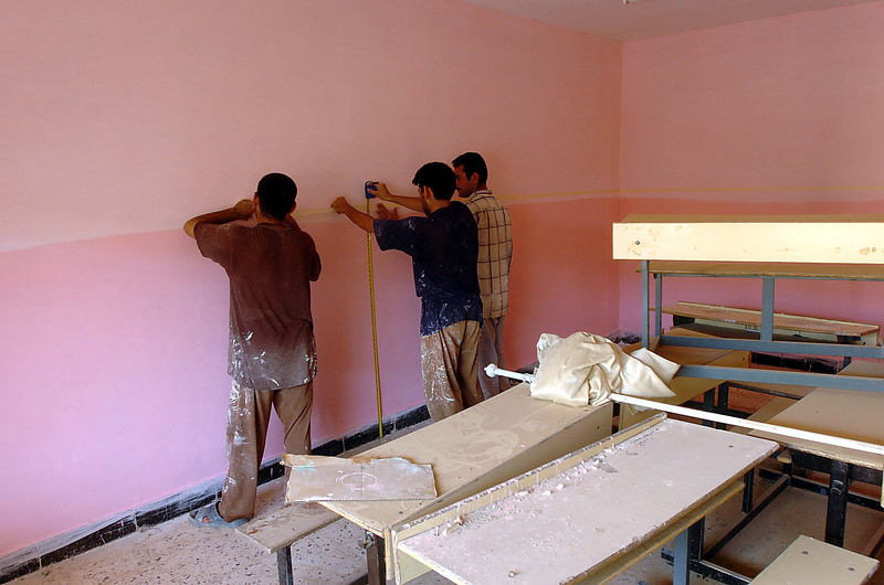 Getting classrooms ready for the school year, these men are painting one of the classrooms.