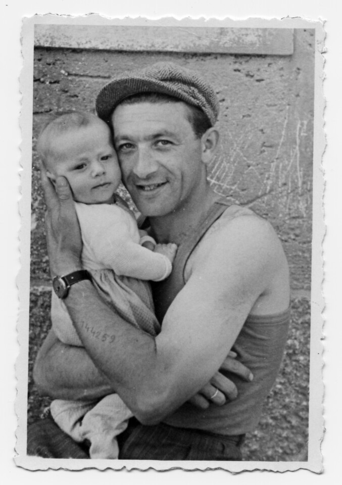 """Joseph with son David<br /> Austria 1947<br /> <br /> May 5th - A Survivor's Story<br />  My father Joseph was liberated from the Mauthausen Concentration Camp by the US 11th Armored Division on May 5th, 1945. That day a pillar was erected on which rested a legacy of Jewish survival, and a model for hope of a better future. The pillar's permanence was assured precisely 30 years later on May 5th, 1975 when my son Josh, Joseph's first grandchild, was born. Recently, after a brief but turbulent struggle, my father lost his battle with cancer. Josh had the honor to be the leader at the last evening service of Shiva, the initial seven day period of mourning. After reciting the Kaddish prayer at the conclusion of the service, he selected as a thought for the day, a passage from Pirkei Avot, a text of Bible commentaries, which proclaims the world is supported by a triad: wisdom from the Torah scrolls, service to God, and acts of kindness. Josh chose well since the portion defined my father's spirit during life. His story is a survivor's story. <br /> <br /> Joseph Greenfield's life spanned most of the 20th century and continued to embrace the new millennium. Along the way, he worked to overcome every obstacle thrust in his path, and engaged every opportunity presented. He approached everything with his good nature, artistry, and the common sense Judaic wisdom he learned (as he used joke) at """"Dombia College,"""" a fictitious institution of higher learning he named after his diminutive Polish home town. He was a gentleman with qualities as beautiful as any of his multi-talents' wondrous creations whether with camera & film, leather, or wood. At all times he maintained a """"shem tov"""", a good name. <br /> He was my hero, and I told him so.<br /> <br /> So what was it like on that long journey? <br /> He witnessed the transition of travel from using a horse and wagon to get to the neighboring town to manned flights to the moon and back. In the one room cheder (school) of Dombia he u"""