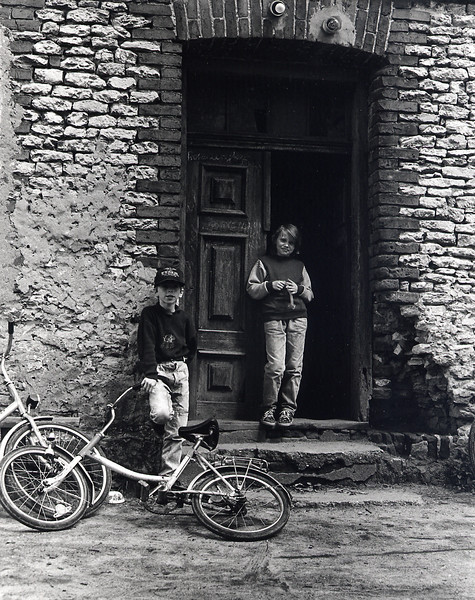 """Young Boys, Dabie 1939<br /> <br /> These boys were at play in front of the house where my father lived. They seemed so carefree, as young teenagers should be during summer months. As I stood there, my thoughts drifted to those precious few quiet moments when my father would give me a vignette of his teenage years in Dabie before the war. He attended """"gymnasium"""", was a member of a Zionist youth movement, and often had coffee and pastries with his girlfriend. Unlike my newfound Polish friends in the doorway, my father would not fully savor his adolescent years since they were suddenly truncated at the start of the occupation. Instead, he grew up much too quickly at places like Mauthausen and Auschwitz."""