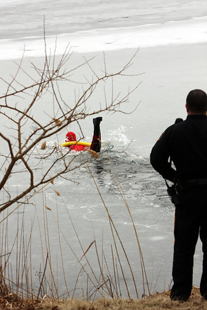 The ice breaking again as he tries to lift himself out of the water onto the ice surface.