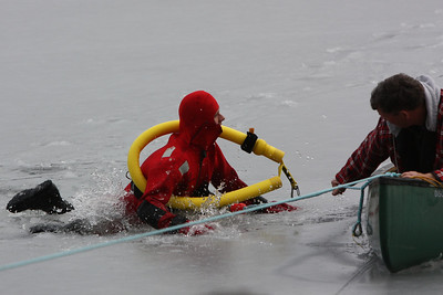 The ice breaks under the weight of the rescuer plunging him back into the water. The man in the canoe attempts to help the rescuer.